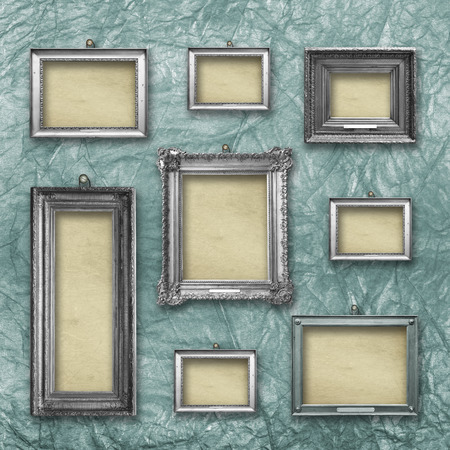 Set of wooden vintage silver  modern,  frames for museum exhibition on old, worn green wall