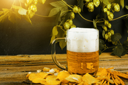 Glass mug of cold fresh golden beer with crackers and chips on wooden table, and branches of ripe hops on dark wall