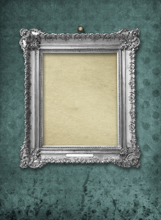 Wooden vintage silver victorian  frame for museum exhibition on old, worn green wall