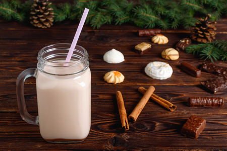 Glass cup of hot cocoa with milk, cinnamon, candies and  straw tube on background of Christmas fir and cones