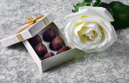 Beautiful white rose with golden gift box and chocolate truffles for Valentines Day or wedding
