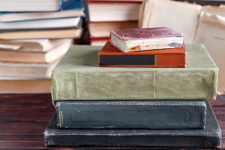 Stack of old vintage books on wooden shelf in  university library for reading