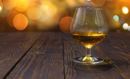 Glass of whiskey or brandy on wooden table on bright glowing background with  beautiful bokeh Stock Photo