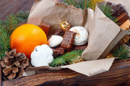 Delicious sweets, chocolates, cookies and oranges for gifts in  wooden box on  vintage table with fir branches