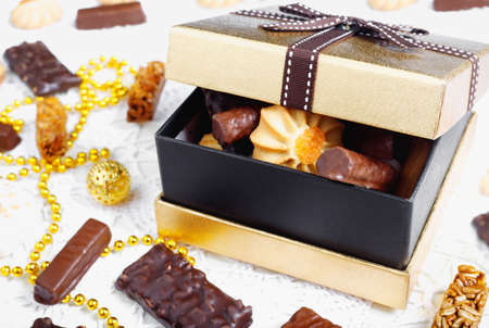 Golden box of chocolates, cookies and biscuits on festive table with beads and balls