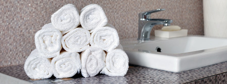 Stack of clean white towels on ceramic countertop in modern bathroom