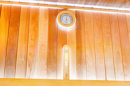 Round thermometer and hourglass on the wall of traditional wooden sauna Imagens