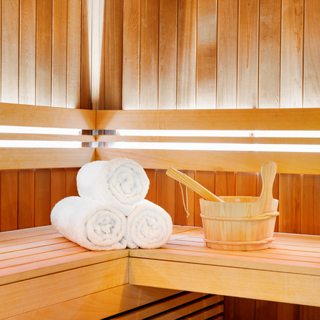 Wooden traditional  sauna for relaxation with bucket of water and set of clean towels