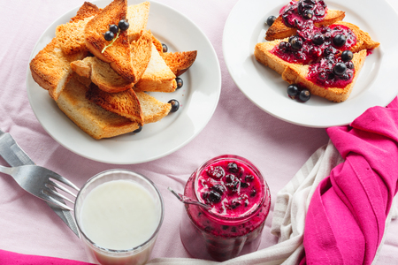 Delicious toasts bread with homemade currant jam with milk on bright crimson tablecloth 写真素材