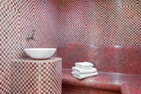 Hammam turc traditionnel avec murs en pierre, évier et pile de serviettes propres