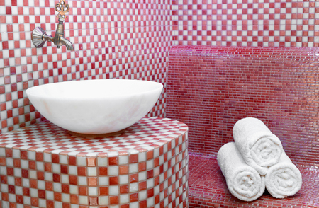 Hammam turc traditionnel avec murs en pierre, évier et pile de serviettes propres Banque d'images
