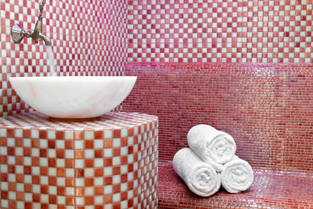 Traditional Turkish hamam with stone walls, sink and stack of clean towels