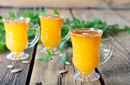 Healthy pumpkin fruit smoothie with seeds and mint leaves on old wooden table
