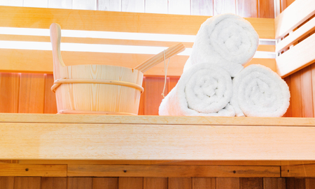 Traditional Finnish wooden sauna for relaxation with bucket of water and set of clean towels