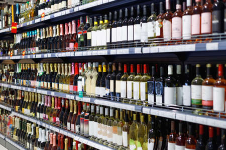 Shelves with variety of alcohol for sale in the supermarket. Vodka, wine, champagne and other alcohol. Foto de archivo