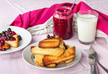 Köstliches Toastbrot mit hausgemachter Johannisbeermarmelade mit Milch auf hellrotem Tischtuch