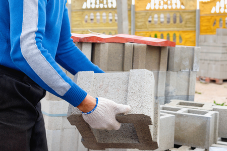 Worker loads cinder blocks  from cement slurry for construction on the  warehouse outdoor Standard-Bild