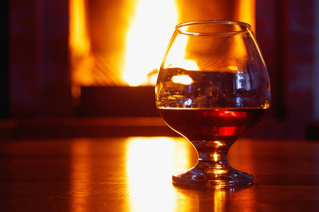 One glass of cognac on background of old brick fireplace with  bright fire