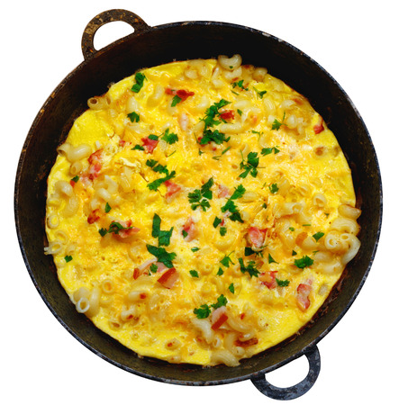 Traditional rustic omelette with bacon, pasta and greens on  old black frying pan on white isolated background.