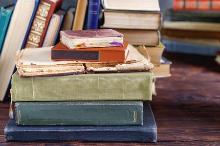 Pila de viejos libros antiguos en estante de madera en la biblioteca de la universidad para leer Foto de archivo
