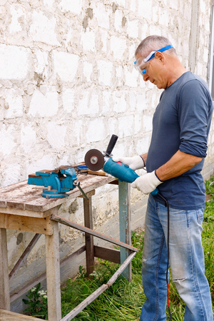 Diligent efficient serious worker makes repairs  with electric tools  hammer and  pliers in backyard of house in outdoor.