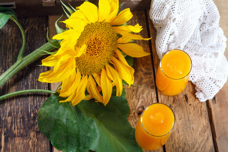 Fresh pumpkin and orange juice with sunflower branches on old wooden wall and lace tablecloth