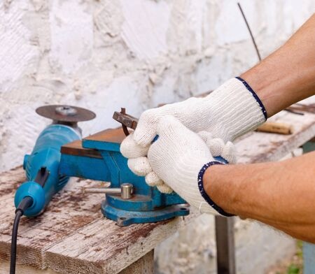 Worker makes repairs  with electric tools  hammer and  pliers in backyard of house in outdoor.