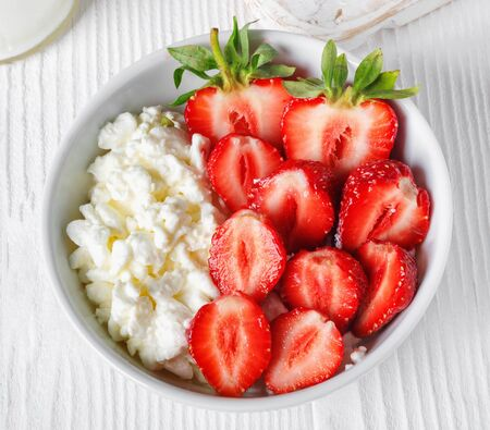 Recipiente blanco con fresas maduras rojas frescas y requesón natural, en la mesa de madera blanca para el desayuno fitness. Vista superior de objetos de grupo laicos planos Foto de archivo