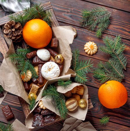 Delicious sweets, chocolates, cookies and oranges for gifts in  wooden box on  vintage table with fir branches. Top view flat lay group objects Stock Photo