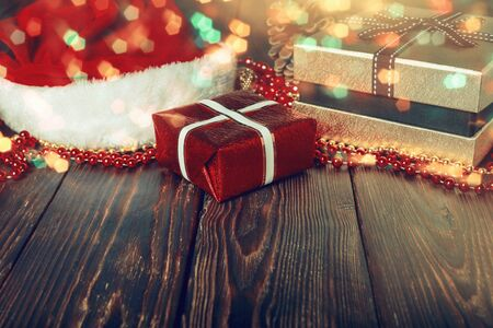 Gift boxes with beads, toys and Santa Claus hat on bright glowing background with lights and bokeh  in Christmas Stock Photo