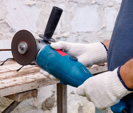 Worker makes repairs  with electric tools  hammer and  pliers in backyard of house in outdoor.  Hand with brush closeup Banco de Imagens