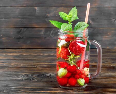 Fresh cool drink of ripe juicy cherry, strawberry, currant and gooseberry berries on  dark wooden table Banque d'images - 124901570