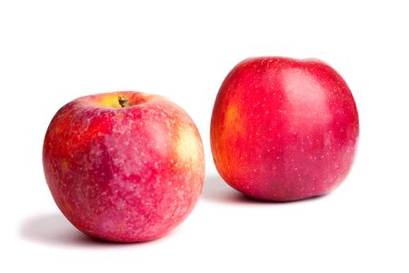 Two red ripe juicy apples on white isolated background with shadow