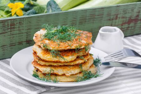 Delicious pancakes from courgettes and fresh vegetables with sour cream and dill in the garden background