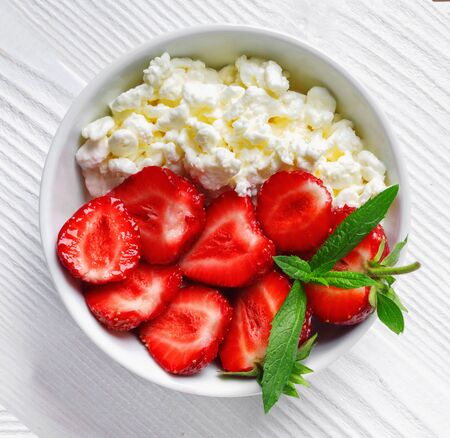 White bowl with fresh red ripe strawberries and natural cottage cheese, on  white wooden table for fitness breakfast. Top view flat lay group objects Banque d'images - 124901821