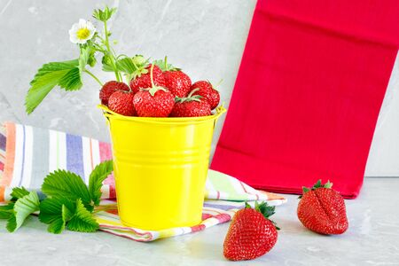 Juicy ripe tasty strawberries in  yellow metal bucket with striped towel on stone countertop. Summer harvest Stock Photo