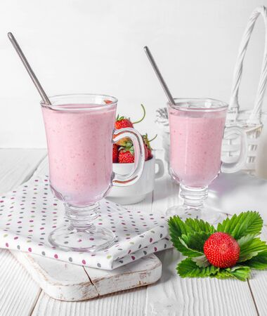 Glass of fresh strawberry and yogurt smoothie on white wooden table for fitness breakfast.