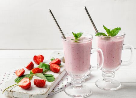 Glass of fresh strawberry and yogurt smoothie on white wooden table for fitness breakfast