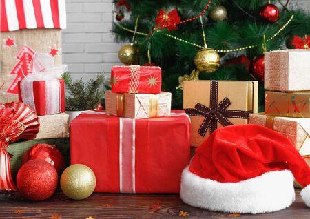 Cajas de regalo con abalorios, juguetes y gorro de Papá Noel en la mesa de madera vintage en Navidad