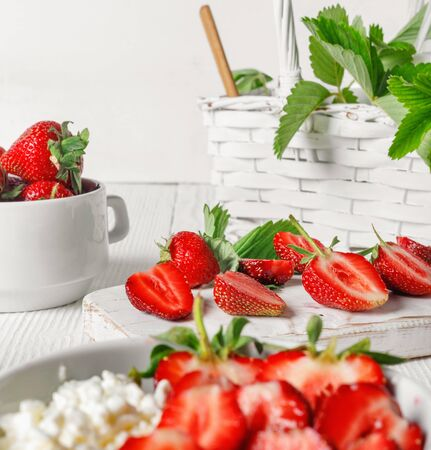 White bowl with fresh red ripe strawberries and natural cottage cheese, on  white wooden table for fitness breakfast.  Zdjęcie Seryjne