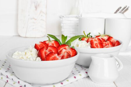 White bowl with fresh red ripe strawberries and natural cottage cheese, on  white wooden table for fitness breakfast.