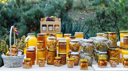 Assortment of honey jars at market stall. Sale of natural honey in fair outdoor. Production of honey.