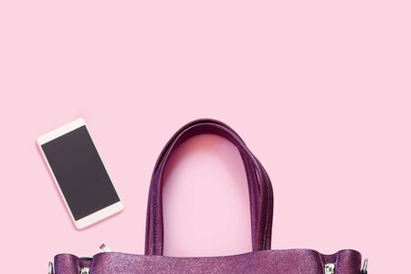 Beautiful fashionable purple bag with new smartphone  wallet on  delicate pink background. Flat lay Top view with copy space for  your text.