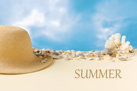 Beautiful straw hat with shells on the ocean coast and blue sky. Nature summer background. Flat lay, top view, copy space concept.