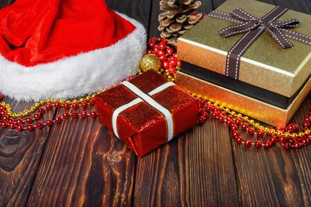 Gift boxes with beads, toys and Santa Claus hat on vintage wooden table  in Christmas