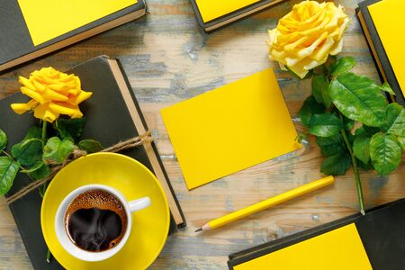 Bouquet of beautiful yellow roses with stack of old vintage books and hot coffee on wooden background. Copy space for nostalgic inscription. Flat lay, top view, copy space concept.