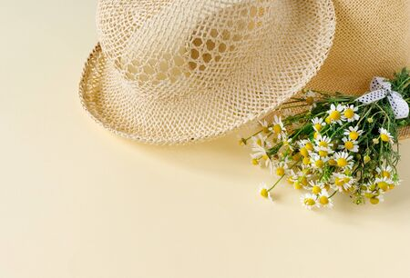 Beautiful straw hat with  bouquet of daisies on sand sunny day. Nature summer background.  Creative greeting card