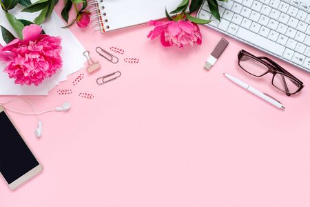 Laptop, accessories and bouquet of beautiful peonies with glasses and headphones on pink background. Flat lay of working place.   Top view  concept, copy space frame for text.