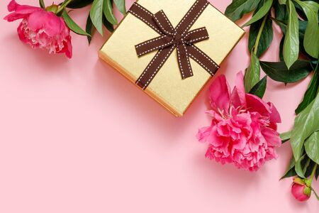 Golden festive box with bow and  bouquet of beautiful peonies on pink background. Holiday concept with empty place for invitation. Flat lay, top view, copy space creative.