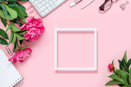 Laptop, accessories and bouquet of beautiful peonies with paper frame, glasses and headphones on pink background. Flat lay of working place.   Top view  concept, copy space frame for text.